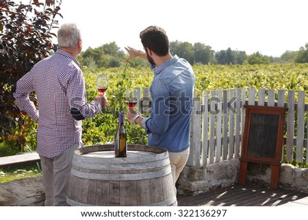 Portrait of multi generations winemakers tasting red wine while standing at vineyard. Small business. - stock photo