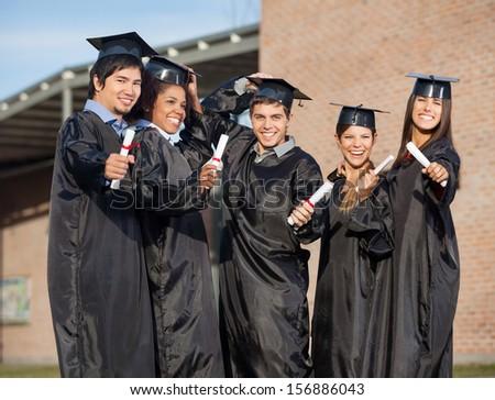 Portrait of multiethnic graduate students holding certificates on university campus - stock photo