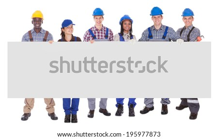Portrait of multiethnic manual workers holding blank banner against white background - stock photo