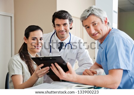 Portrait of multiethnic medical professionals smiling while standing at hospital reception - stock photo