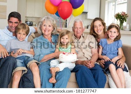 Portrait of multigeneration family celebrating girls birthday in living room - stock photo