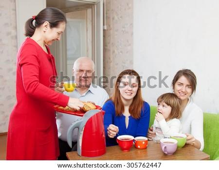 Portrait of multigeneration family having tea with cakes - stock photo