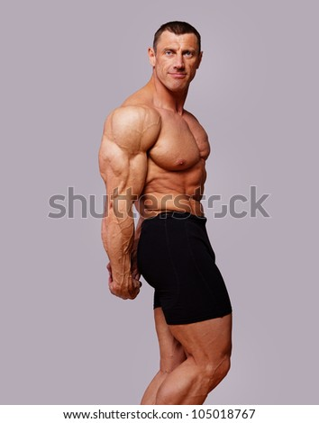 Portrait of muscle man posing in grey background - stock photo