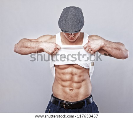 Portrait of muscle man posing in studio in hat showing his abs - stock photo