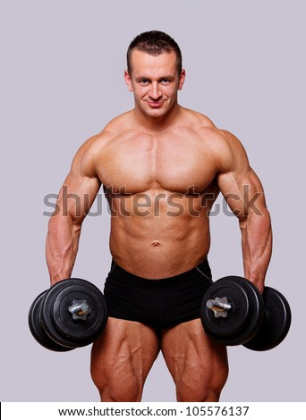 Portrait of muscle man posing in studio with dumbbells - stock photo