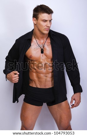 Portrait of muscle man posing on a grey background - stock photo