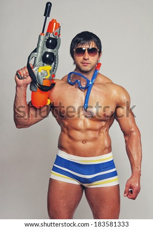 Portrait of muscle man posing on the beach with water gun - stock photo