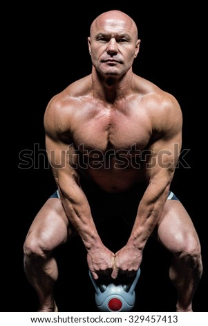 Portrait of muscular man exercising with kettlebells against black background - stock photo