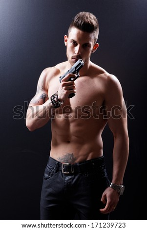 Portrait Of Muscular Man With Gun On Black Background .Low light. - stock photo