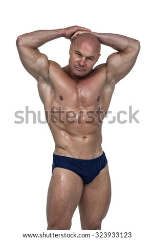 Portrait of muscular man with hands behind head standing white background - stock photo