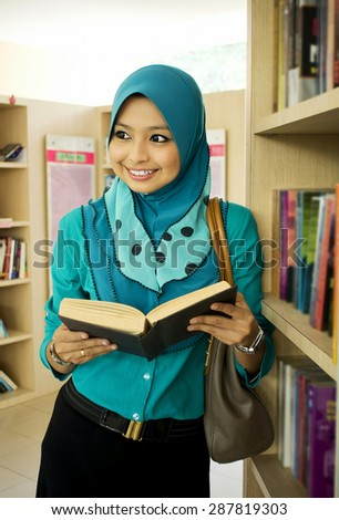Portrait of Muslim student reading book in the library - stock photo