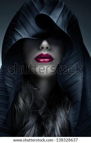 Portrait of mysterious woman in dark hood - stock photo