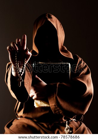 Portrait of mystery preaching monk with wooden rosary and bible - stock photo