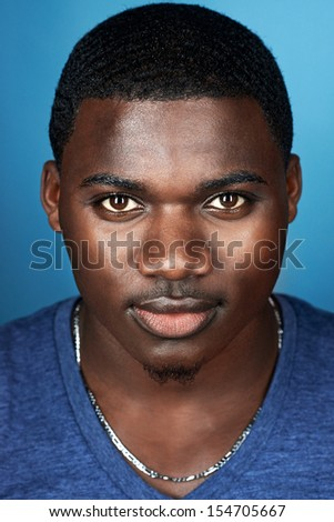 portrait of natural real african man on blue background - stock photo