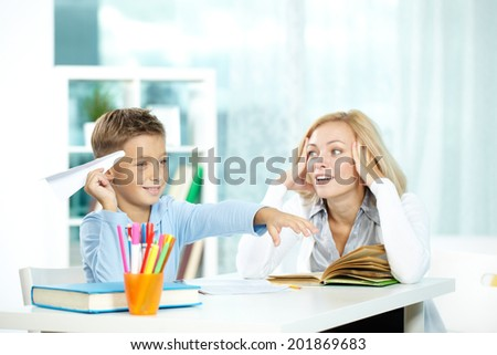 Portrait of naughty boy playing with paper plane during lesson and discontent tutor touching her head - stock photo