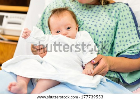 Portrait of newborn baby girl sitting with mother lap in hospital room - stock photo