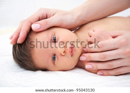 Portrait of newborn baby in careful mothers hands - stock photo