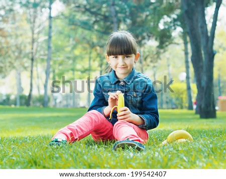 Portrait of nice caucasian girl kid clean fresh banana in summer outdoors - stock photo
