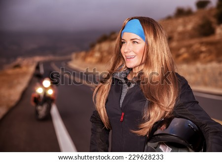 Portrait of nice happy young biker on the road, beautiful girl enjoying extreme sport, bike ride adventures, active lifestyle - stock photo