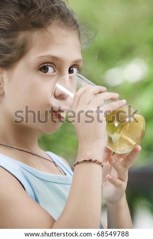 portrait of nice little girl drinking juice in summer environment - stock photo