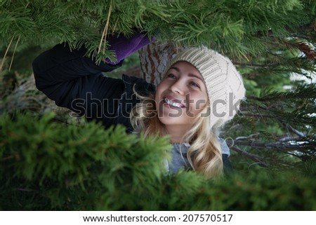Portrait of nice smiling woman in x-mas tree surrounding - stock photo