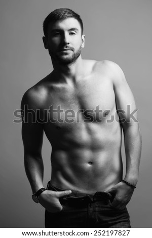 Portrait of nude muscular handsome fitness male model in jeans. - stock photo