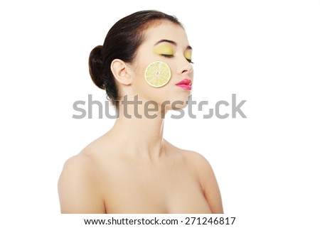 Portrait of nude woman with lemon on cheek. - stock photo