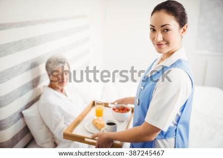 Portrait of nurse giving breakfast to senior woman in bedroom - stock photo