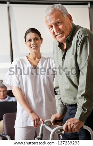 Portrait of nurse helping senior male patient to use walker with person sitting in background - stock photo