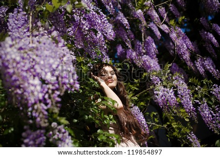 Portrait of of beautiful girl standing in the park among flowers - stock photo