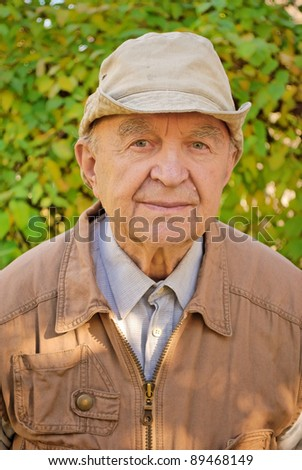 portrait of old man in garden - stock photo