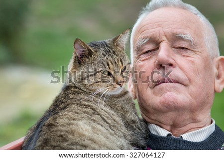 Portrait of old man with his tabby cat on his chest - stock photo
