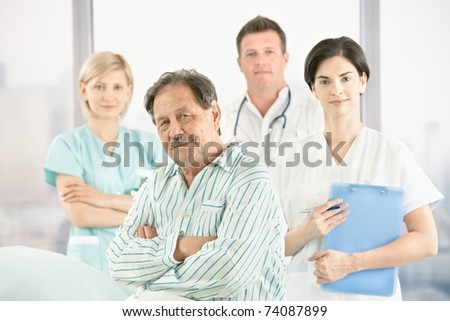 Portrait of old patient with doctors and nurse in hospital, looking at camera.? - stock photo