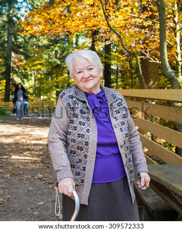 Portrait of old smiling woman in autumn park - stock photo