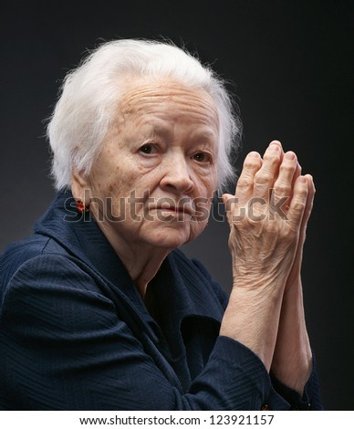 Portrait of old woman on a gray background - stock photo