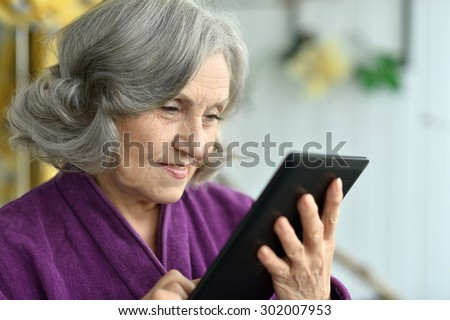 Portrait of Old woman with tablet pc - stock photo