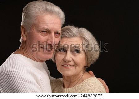 Portrait of older couple embracing on a black background - stock photo