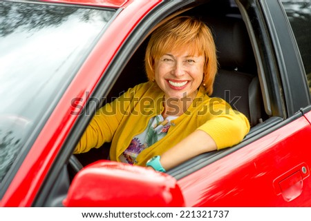 Portrait of older woman driving a car - stock photo