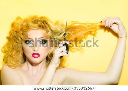 Portrait of one beautiful sensual sexy young retro blonde woman with curly hair and bright red lips looking forward holding scissors in studio on yellow background, horizontal picture - stock photo