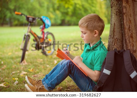Portrait of one cute boy, he draws in park - stock photo