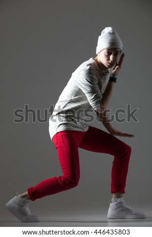 Portrait of one funny hipster young man dancing wearing casual red jeans and beanie. Modern style cool dancer guy working out. Full length photo image on studio gray background - stock photo