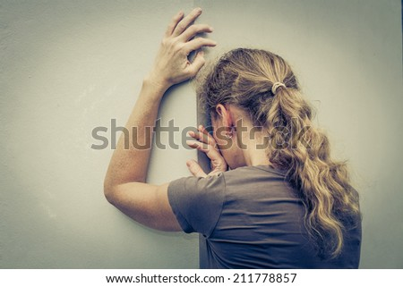 portrait of one sad woman standing near a wall  - stock photo