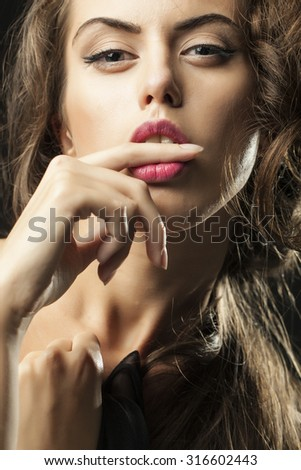 Portrait of one sensual young woman with big eyes pink lips and stylish haircut holding finger in open mouth looking forward closeup, vertical picture - stock photo