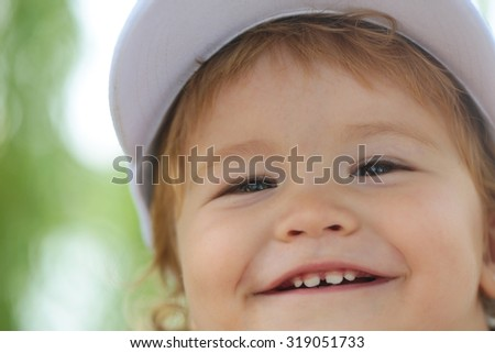 Portrait of one small happy smiling male child swith blond curly hair in white cap on green natural blur background closeup, horizontal picture - stock photo