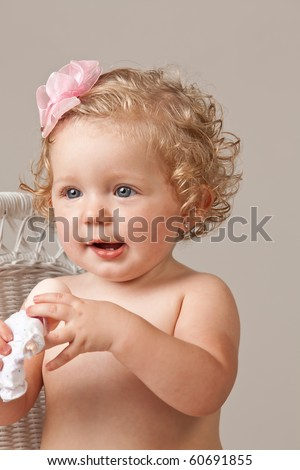 Portrait of one year old baby girl wearing pink bow in hair holding a toy doll. - stock photo