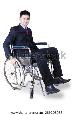 Portrait of optimistic disabled entrepreneur smiling on the camera while sitting on the wheelchair - stock photo