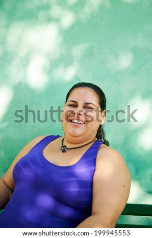 Portrait of overweight hispanic woman looking at camera and smiling - stock photo
