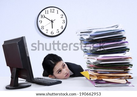 Portrait of overworked businesswoman looking at pile of documents - stock photo