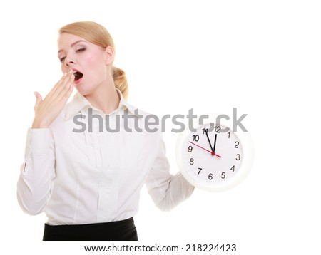 Portrait of overworked businesswoman showing clock. Sleepy blond girl yawning isolated on white. Time management and long working hours. Studio shot. - stock photo
