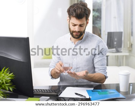 Portrait of overworked young businessman takes the medicine while sitting at workplace in front of computer.  - stock photo